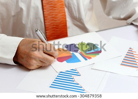 businessman is writing on different documents with graph