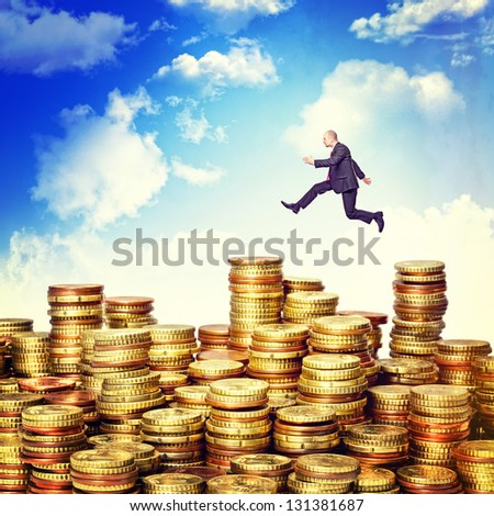 businessman jump over euro coin piles