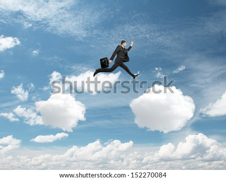 businessman jumping from cloud to another cloud - stock photo