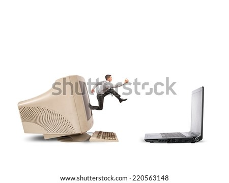 Businessman jumping from old computer to new laptop - stock photo