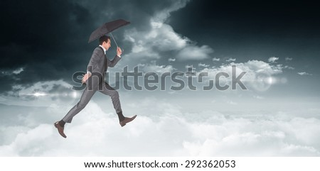 Businessman jumping holding an umbrella against bright blue sky with clouds