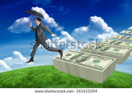 Businessman jumping holding an umbrella against green field under blue sky - stock photo