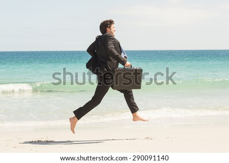 Businessman jumping in front of the sea at the beach