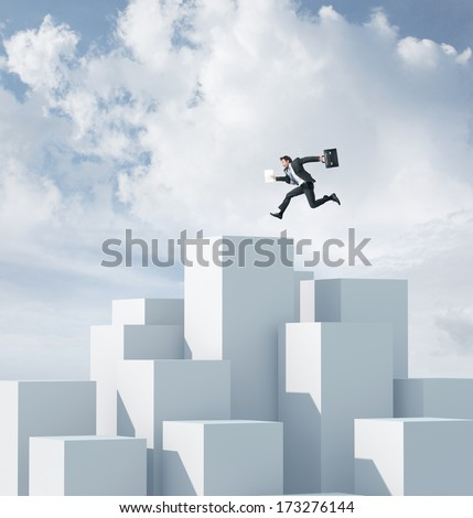 Businessman jumping on a highest cube - stock photo