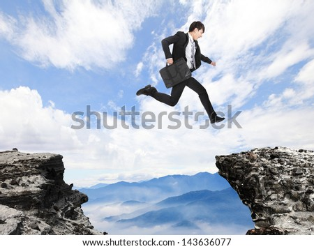businessman jumping over danger precipice on the mountain, concept for business, asian people