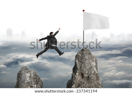 businessman jumping over mountain peak to blank flag with gray cloudy cityscape background - stock photo