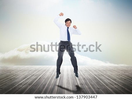 Businessman jumping over wooden boards leading out to the horizon with his fist in the air