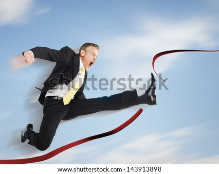 Businessman jumping through red tape against the sky