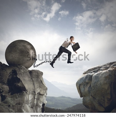 Businessman jumps the obstacle with the weight - stock photo