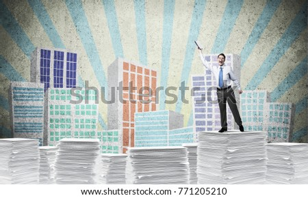 Businessman keeping hand with book up while standing on pile of paper documents with drawn cityscape on background. Mixed media.