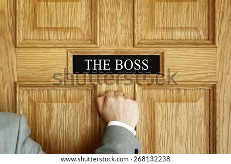 "Businessman knocking on a door to ""The Boss"" office concept for meeting, trouble, problems, promotion or being fired - stock photo"