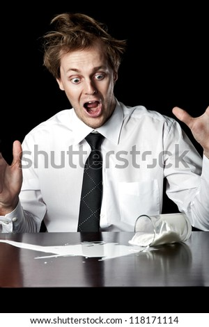 Businessman knocks over glass of milk, exclaims in horror, conceptual image desaturated with black background - stock photo