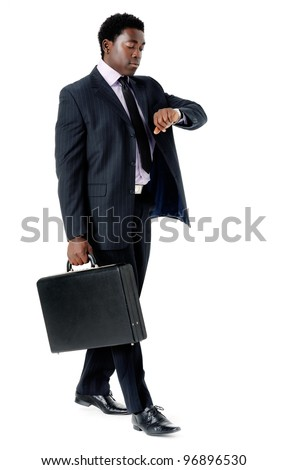 Businessman late for a meeting checking the time and walking with briefcase isolated on white - stock photo