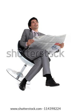 Businessman laughing at a newspaper - stock photo
