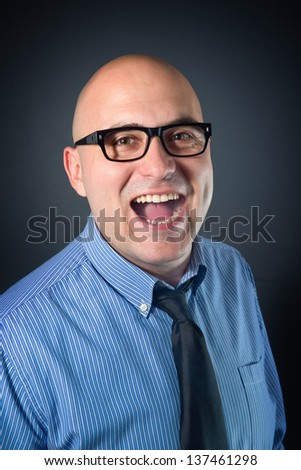 Businessman laughing. Bald business man in blue shirt laughing with his mouth wide open.