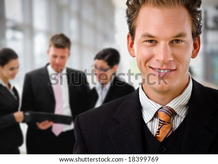 Businessman leading team of business people working in background. - stock photo