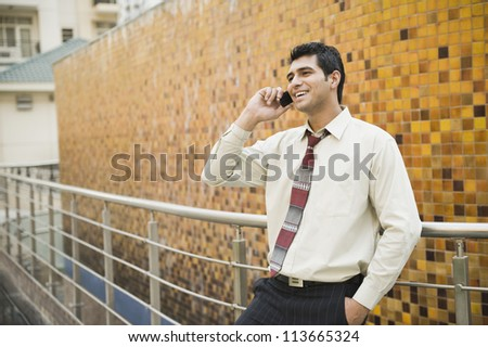 Businessman leaning against a railing and talking on a mobile phone