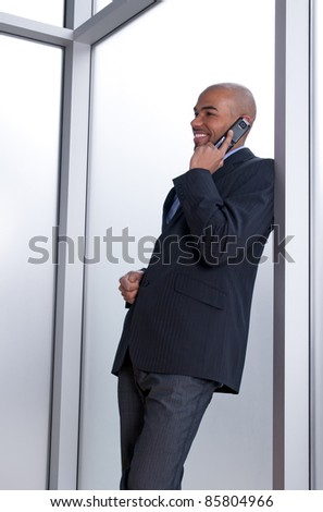 Businessman leaning against the window, talking on the phone and smiling.