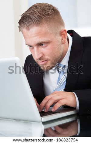 Businessman leaning forward staring intently at his laptop screen as he types information on the keyboard while sitting at his desk  close up portrait - stock photo