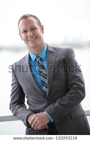 Businessman leaning on a rail - stock photo