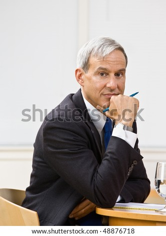 Businessman leaning on table - stock photo