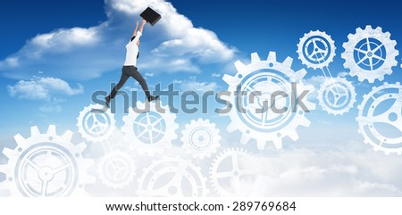 Businessman leaping with his briefcase against bright blue sky with clouds - stock photo