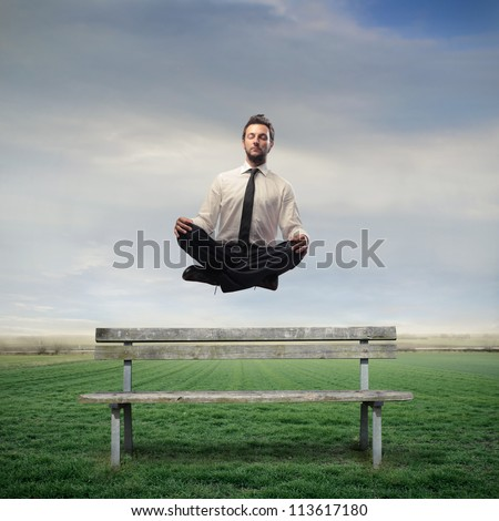 Businessman levitating on a bench - stock photo