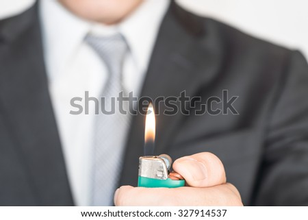 Businessman light a lighter