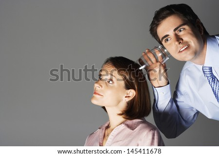 Businessman listening through glass to woman's head against gray background - stock photo