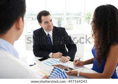 Businessman listening to ideas of designers team