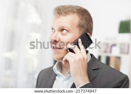 Businessman listening with anticipation to a call on his mobile phone standing looking up into the air with parted lips