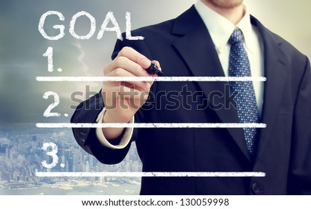Businessman listing his goals with cityscape background - stock photo