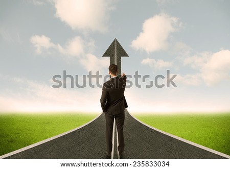 Businessman lokking at 3d road upgoing arrow concept - stock photo