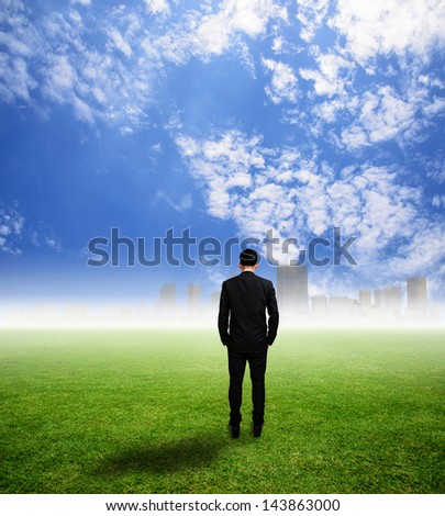 Businessman look city on grass field