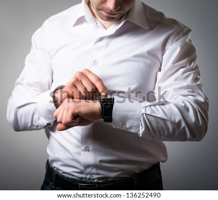 Businessman look his watch  on a grey background - stock photo
