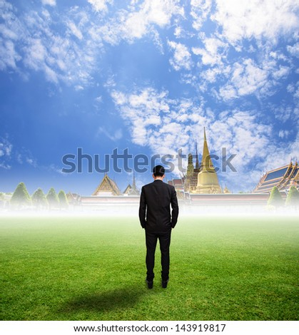 Businessman look temple on grass field