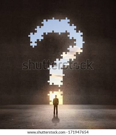 businessman looking an big question mark in dark room - stock photo