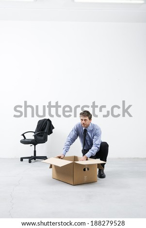 Businessman looking around and packing with cardboard box in an empty office.