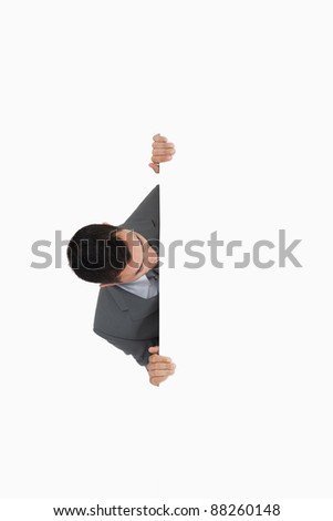 Businessman looking around the corner against a white background
