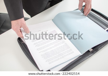 Businessman looking at a document in his briefcase - stock photo