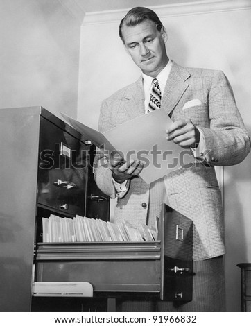 Businessman looking at a paper next to a filing cabinet