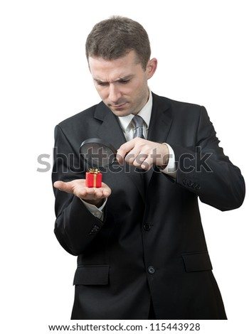 Businessman looking at a small present with a magnifying glass - stock photo