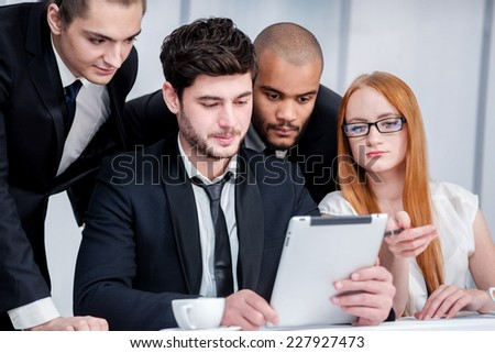 Businessman looking at a tablet. Four smiling successful businessmen sitting at table in office while discussing their business doings. Young people talking in office