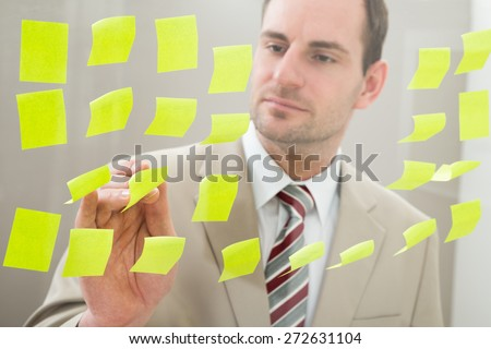 Businessman Looking At Adhesive Notes On Glass Wall