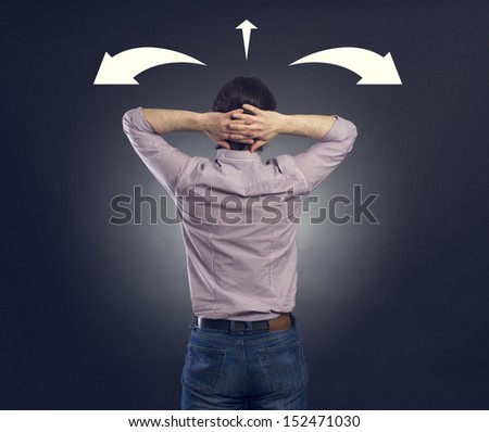 Businessman looking at arrows pointed in different directions - stock photo