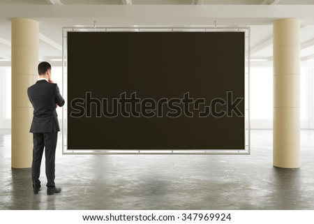 Businessman looking at blank blackboard in sunny spacious hangar area with concrete floor, mock up 3D Render - stock photo