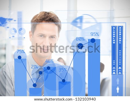 Businessman looking at blue futuristic diagram interface with colleague behind him - stock photo