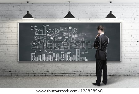 businessman looking at business strategy on blackboard - stock photo