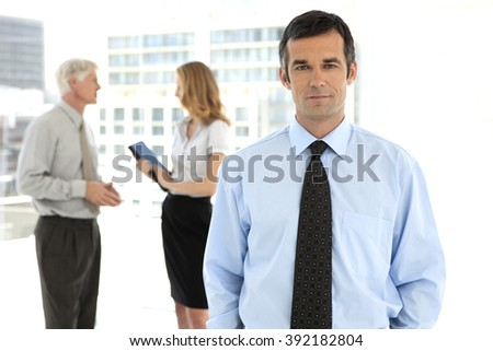 Businessman looking at camera on foreground and business people talking in the background - stock photo