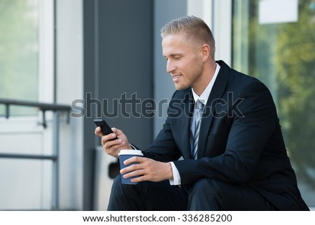 Businessman Looking At Cellphone Holding Disposal Cup - stock photo